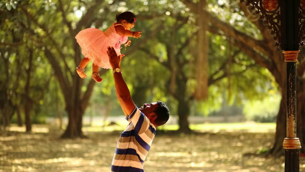 A young man throwing and catching his daughter above his head