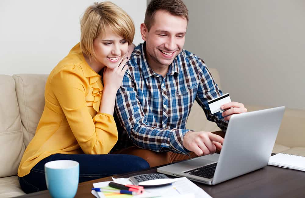 A young couple sitting together on the sofa, checking their credit rating on their laptop.