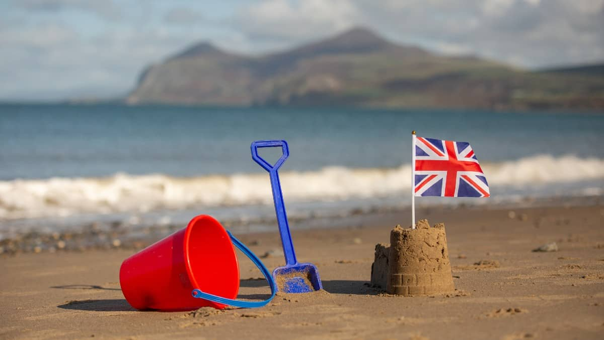 Union Jack flag in a castle shaped sandcastle on a beautiful beach in brilliant sunshine